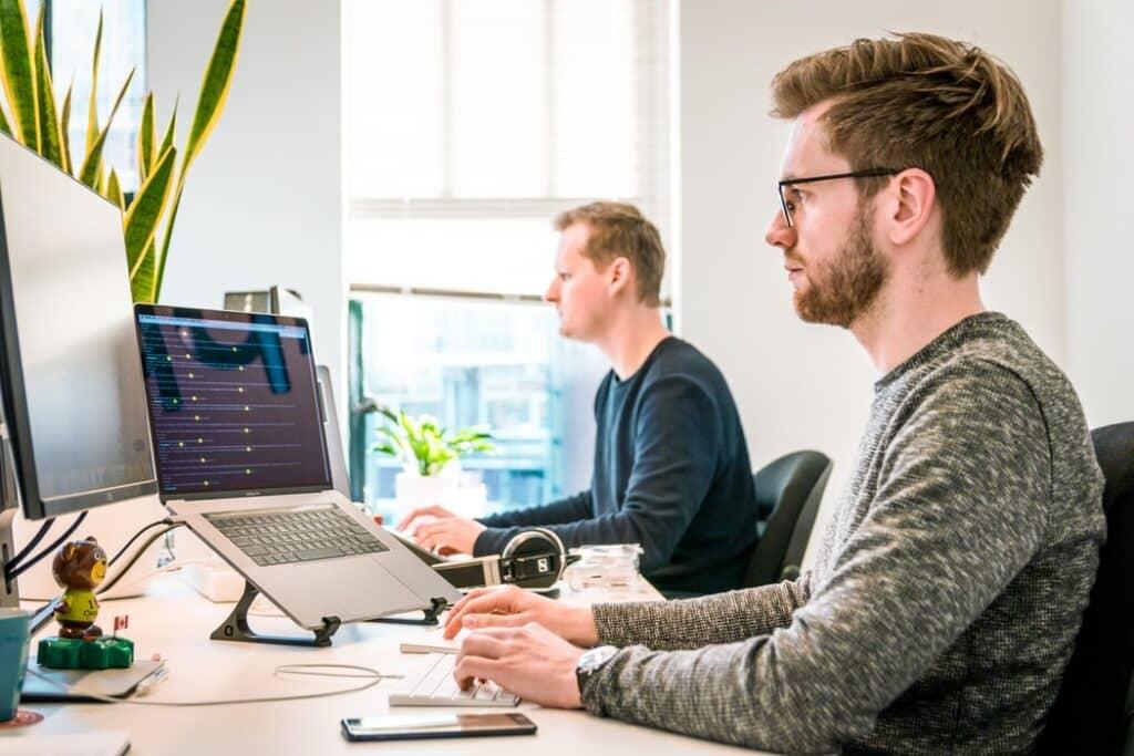 Twee werknemers aan het werk voor computer